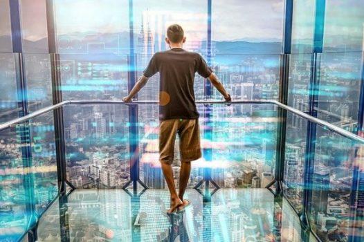 Ragazzo di spalle ammira il panorama dall'interno di un ascensore con le pareti in vetro